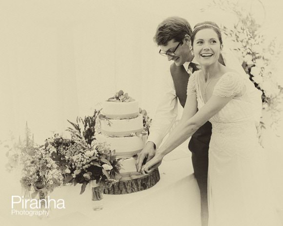 Bride and groom cutting cake in marquee