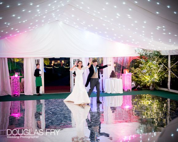 Bride and groom entering marquee - mirrored dance floor
