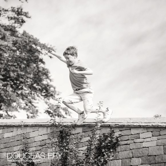 Boy jumping off wall - family photograph