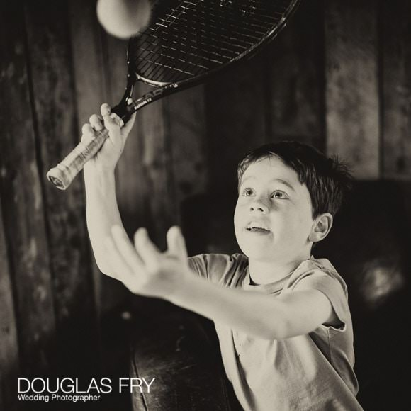 Black and white photograph of boy playing tennis