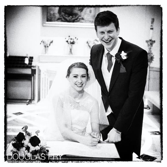 Bride and groom in black and white signing the register in Church