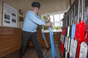 Ex-GNR(I) man Willie Gault, who worked similar signal cabins in Fermanagh, has a go at the levers in Downpatrick East Cabin. (Photo: Bernie Brown)