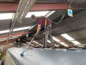 A volunteer at work on the roof of an 80 class carriage. He is wearing a harness attached to a safety line in the workshop ceiling, and is painting the carriage roof grey with a roller.