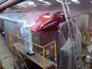 A painter in disposable overalls and mask is spray painting the dome end of the roof of the 80 class driving carriage. The carriage is sheeted off with plastic to protect the other paintwork. The new paint is a shiny maroon colour.
