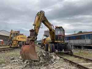 Two road-rail excavators being used to clear rubble and old rails around tracks.