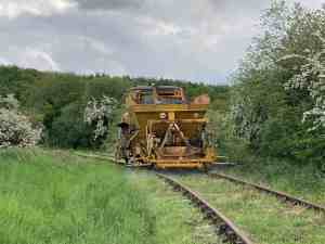 A large yellow track machine with a weed spraying attachment drives slowly round a curve on our railway line. The track is overgrown with weeds and grass.