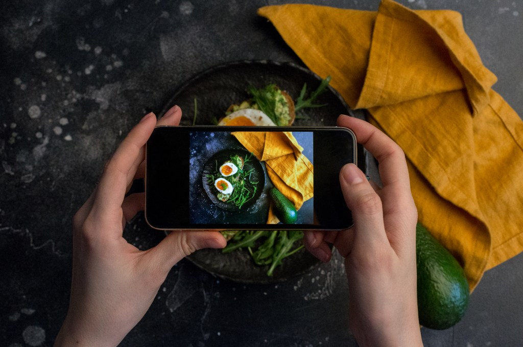 Taking photo of sandwich with eggs with smart phone at dark background