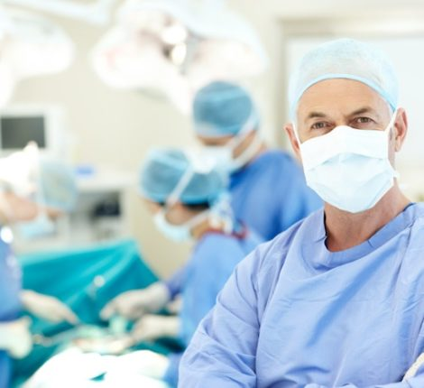 Portrait of a senior surgeon wearing a face mask and hospital scrubs in an operating theatre - Copyspace