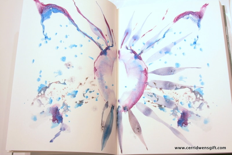Journal pages with inkblot and squiggle-doodles.