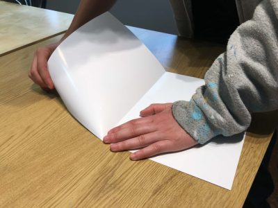 Photo showing the beginning of the process of tearing watercolor paper. Roll the corner underneath; pull away from the crease at a 45 degree angle.