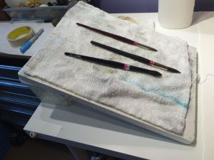 Watercolor brushes drying on a towel on a slanted board.