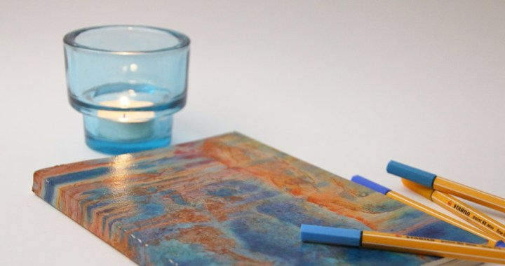 journal with pens and candle