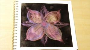 """Flower"" design in metallic ink on black surface."