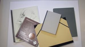 hardbound and spiral bound sketchbooks and a portfolio