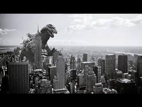 black and white image of godzilla over city