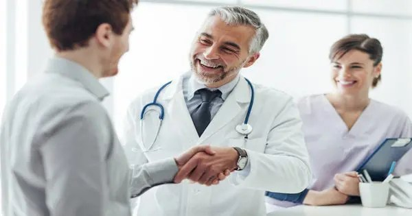 blog de imágenes de pacientes que sacude la mano del doctor con la enfermera o asistente en el fondo