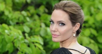 blog picture of angelina jolie turning around for the camera in front of foliage