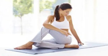 blog picture of lady sitting on mat stretching out her legs