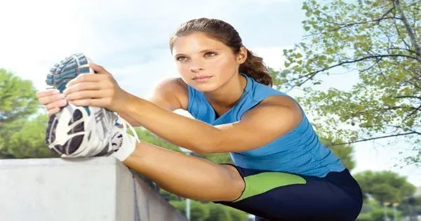 blog picture of young lady stretching leg outside before running