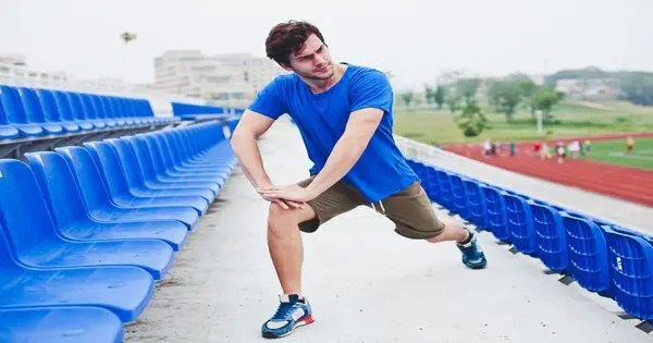runner stretching leg out in stadium seats
