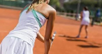 blog picture of a young girl playing doubles tennis about to serve