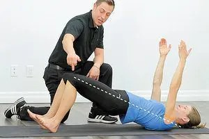 blog picture of trainer working with a lady that is laying down raising her lower body feet still on the ground and arms raised