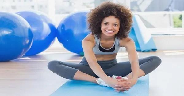 blogunda, yoga stüdyosunda oturan bayan, iç bacakları için kelebek gerginliğini yapıyor