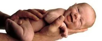 blog picture of naked baby being held by chiropractor