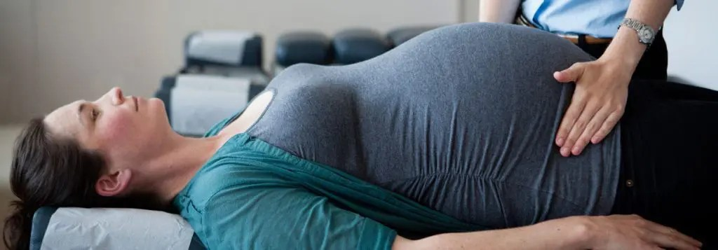 bog picture of pregnant woman being checked by chiropractor