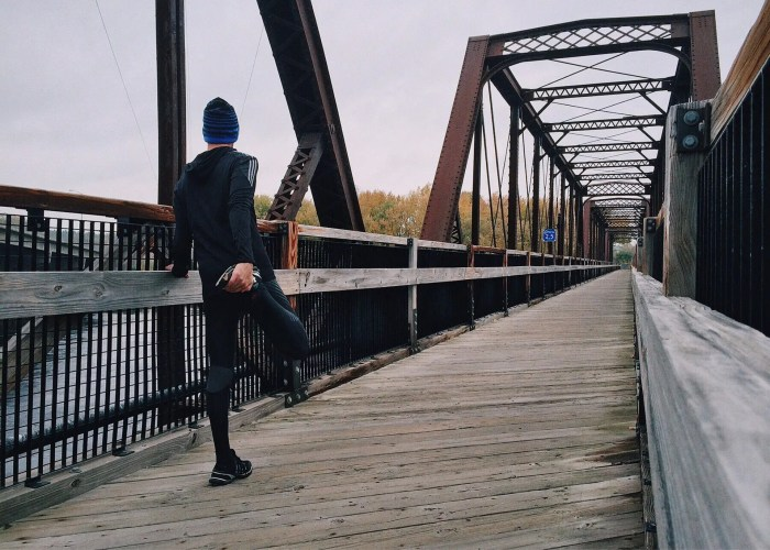 blog picture of a man stretching leg before running down a bridge