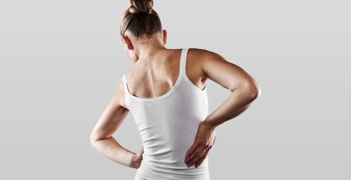 joven mujer en camisa blanca sufriendo de escoliosis de dolor de espalda