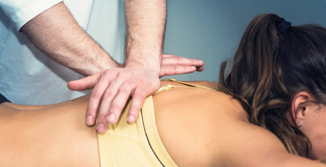 chiropractor doing a spinal adjustment on lady
