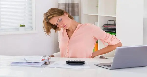 lady at desk with back pain from incorrect posture