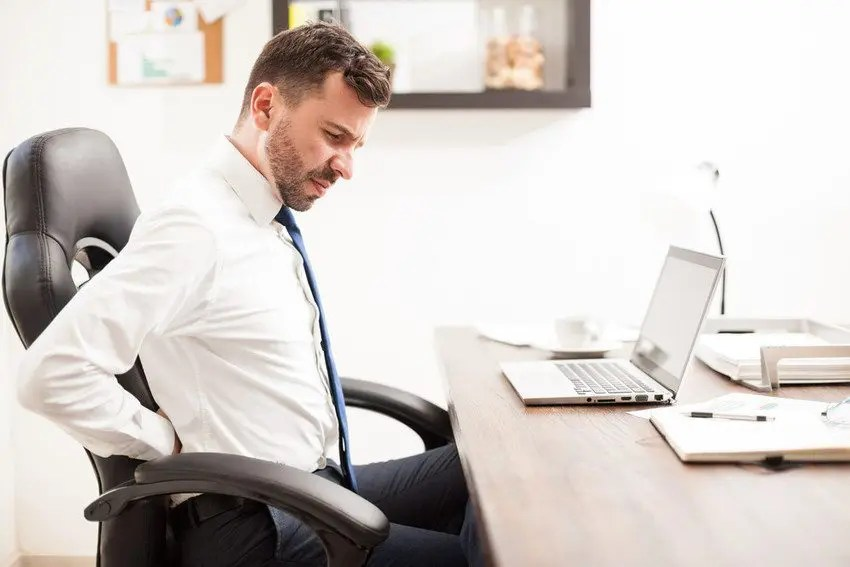 Hombre en silla de oficina con dolor lumbar