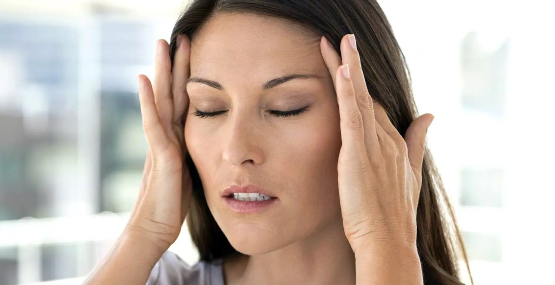片頭痛の女性の寺院をつかむ