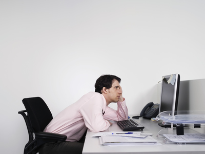 working man sitting at desk slouched