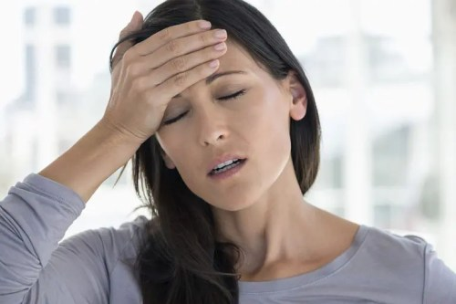 Image of a woman with a migraine holding her head.