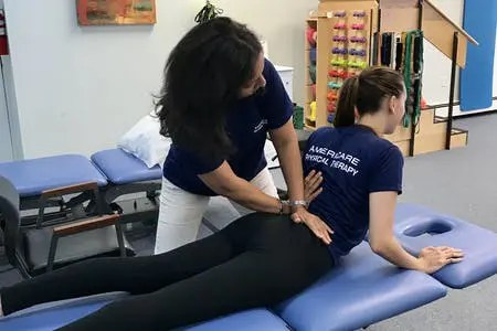 Woman Performing the McKenzie Method on a Patient