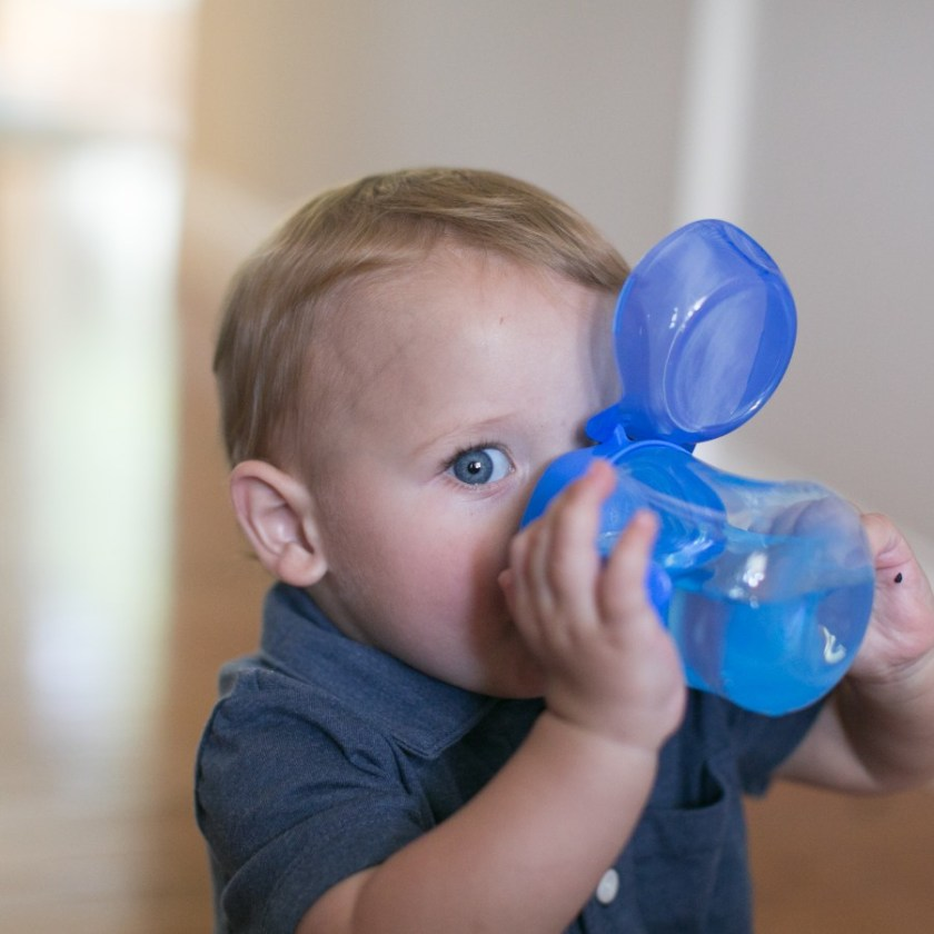 Baby drinking from blue cup
