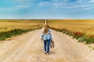 rezygnacja kobiety z walizką na drodze