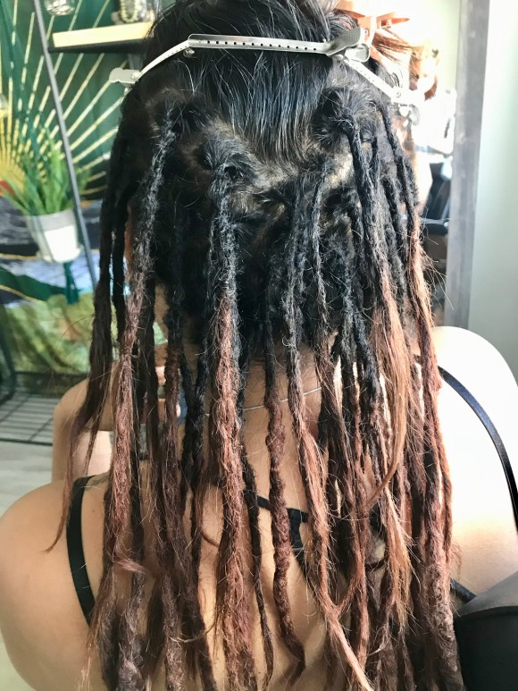 The purpose of this image is to show the clean sections of a client's partial dreadlocks following her root maintenance appointment.