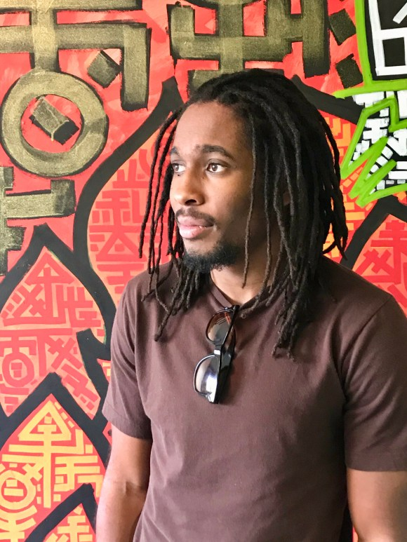 This is a picture of a man with shoulder-length dreadlocks following maintenance