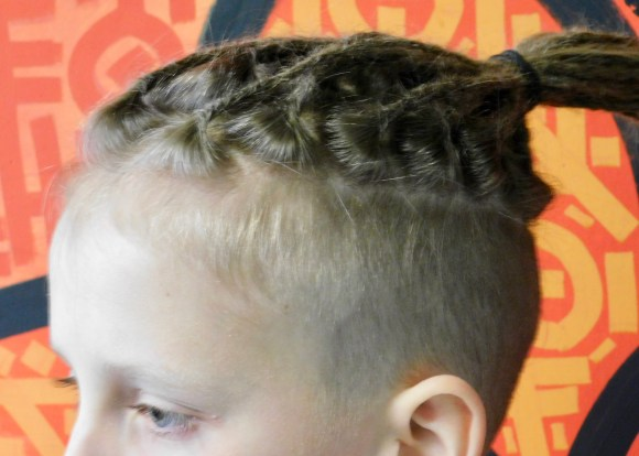 This image shows the roots of partial dreadlocks left intentionally loose. The subject is a 12-year-old child with crochet dreadlocks on top of his head.