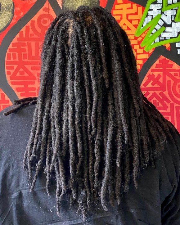 A picture of dreadlocks following a dreadlock repair appointment. His dreads go down to his mid-back.