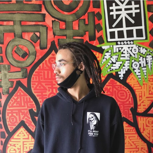 A picture of a client following a dreadlock installation appointment. He's wearing a black hoodie, glasses and is looking to one side. His dreadlocks are nearly shoulder-length.