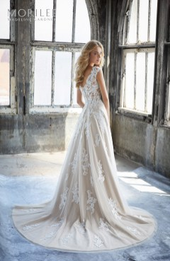 Kennedy Wedding Dress Slim A-Line Wedding Dress Featuring an Elaborately Beaded and Embroidered V-Neck Bodice with Appliqués on English Net. A Zipper Back Closure Trimmed in Covered Buttons Completes the Look. Matching Satin Bodice Lining Included. Shown in Ivory/Rosé