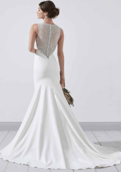 PC8350 A sophisticated mermaid style, with a high neckline finished in striking hand beaded detail. The beautiful hand beaded detail is continued on the stunning illusion back. Zip back and buttons. Available in Ivory Only. Photographed in Ivory.