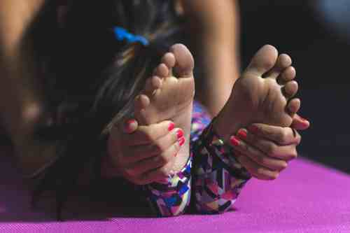 Woman holding feet in pilates pose