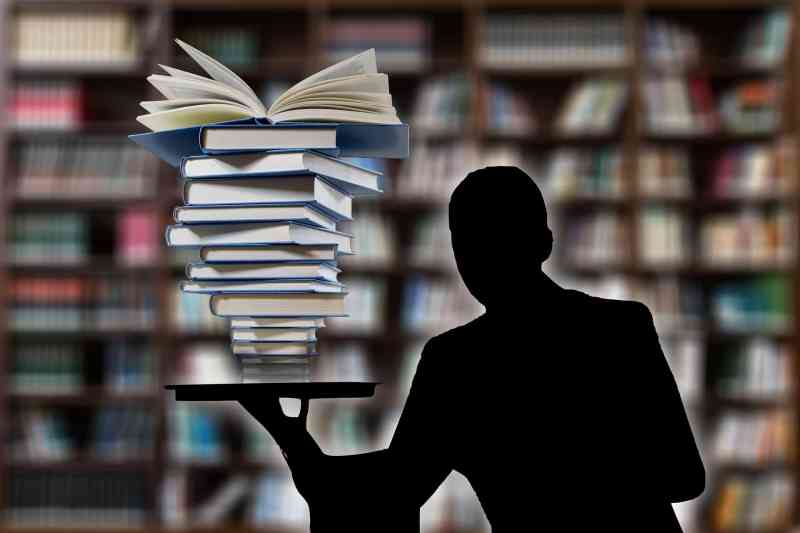 Dictionary of marketing terms - stack of books and silhouette of man representing a stack of marketing terms