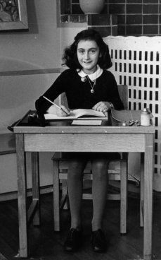 Anne Frank at desk reading a book